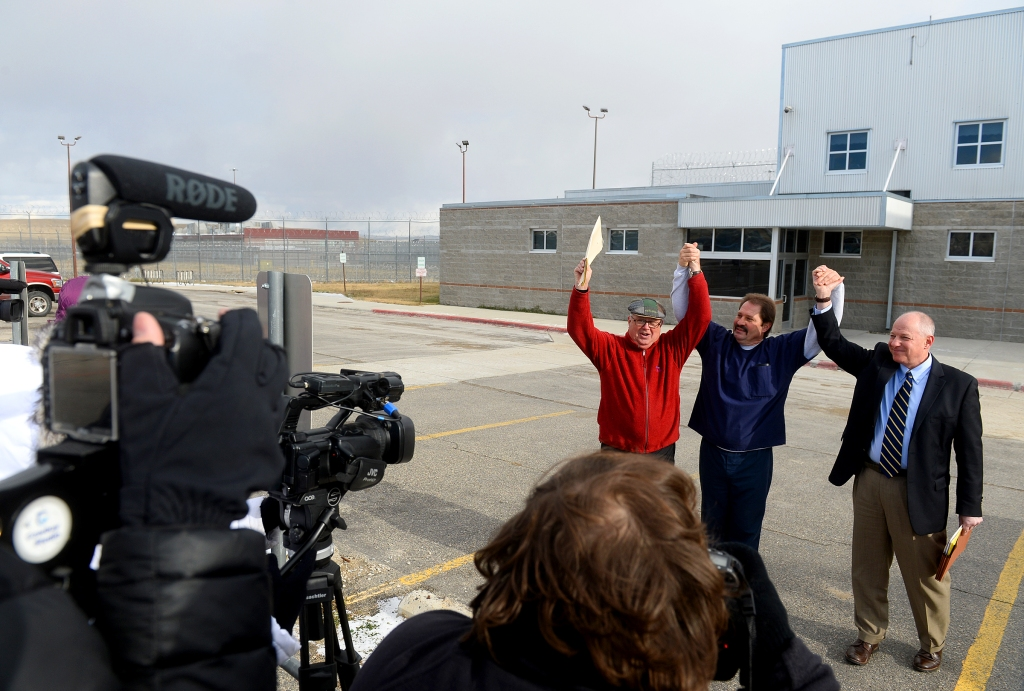 Barry Beach, center, flanked by Jim McCloskey of Centurion Ministries, left, and attorney Peter Camiel, raise their arms in victory during a meeting with the press outside of the of the Montana State Prison in Deer Lodge, on Nov. 20, 2015. Gov. Steve Bullock commuted Beach's 100-years-without parole prison sentence, after Beach served more than 30 years in prison for a murder he says he didn't commit.  - Photo Courtesy Rion Sanders, Great Falls Tribune.